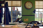 """© Licensed to London News Pictures. 13/03/2013. Duxford, UK Les Millgate, a fighter pilot based at Duxford in the 1950's with No. 64 Squadron, looks throughout the window of the recreated Watch Office, a forerunner to the control tower. Press preview today 13th March 2013 of """"Historic Duxford"""" designed to explore the RAF's time at the airfield from 1918 to 1961. RAF Duxford is Britain's best preserved Second World War Airfield with a history that dates back to the First World War.  The exhibition opens to the public on the 28th March. Photo credit : Stephen Simpson/LNP"""
