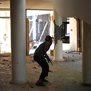 A rebel fighter takes cover during the attack to the Jewel Hotel in central  Zawiyah.