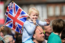 ©  London News Pictures. 21/04/2016. Windsor, UK. A young girl on her fathers shoulders waving the union flag as she watches HRH QUEEN ELIZABETH II in an open top Land Rover with PRINCE PHILIP during a drive through the town of Windsor, Berkshire on the day of her 90th birthday.  Photo credit: Ben Cawthra/LNP