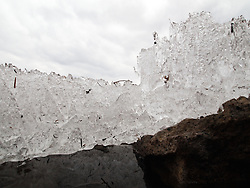 Heaved lake ice sits atop water and rock on the shores of Lake Nokomis in early spring