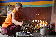 India, Ladakh region state of Jammu and Kashmir, Stakna monastery. A priest lighting candles