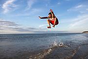 A man jumps on a Cape Cod beach.