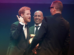Britain Prince Harry (left) receives a posthumous Legacy award on behalf of his mother Diana, Princess of Wales, from Ian Walker, (right) and Julian La Bastide, at the Attitude Awards in London.