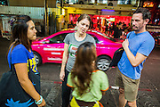 01 APRIL 2013 - BANGKOK, THAILAND:   , Naamfon Boonlab, the Hupes' Thai colleague, Amy Hupe and Tim Hupe talk to a Cambodian girl who works on the streets in the Nana red light district. The girl begs from tourists and also sells roses and flowers to tourists. PHOTO BY JACK KURTZ