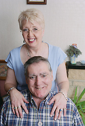 Wife standing behind man with Alzheimer's disease,