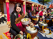14 APRIL 2019 - DES MOINES, IOWA: Women make an offering at the Tak Bat during Lao New Year, also called Songkran,  observances at Wat Lao Buddhavath in Des Moines. Several thousand Lao people live in Des Moines. Most came to the US after the wars in Southeast Asia. Songkran is celebrated in Theravada Buddhist countries (Sri Lanka, Myanmar, Thailand, Laos, and Cambodia) and in Theravada Buddhist communities around the world.        PHOTO BY JACK KURTZ