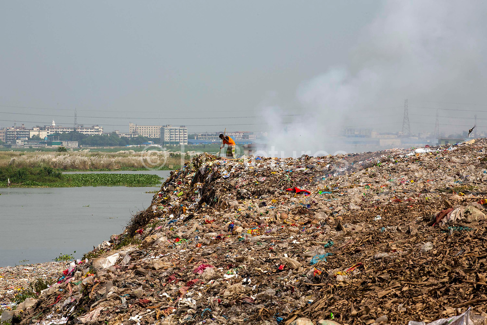 A man searches through a burning rubbish pile on the banks of the Turag river on the 1st of October 2018 in Dhaka, Bangladesh. Environmental pollution next to rivers and lakes is a common sight in Dhaka, polluting water sources that also used for washing and drinking water.