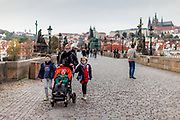 A mother and her three children wearing face masks (except the youngest child) while passing Charles Bridge in Prague. As of 21st of October 2020 people have to wear face masks outside and inside.