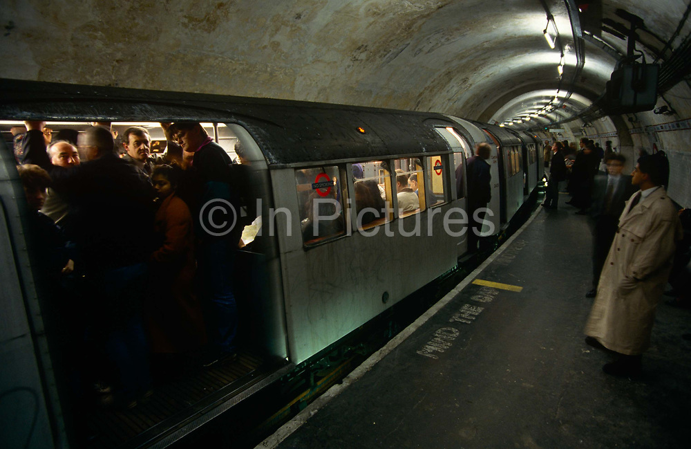 """During the morning rush-hour at Bank underground station in the heart of London's financial district, the grim face of 90s tube travel is seen here in a wide landscape of rounded tunnel and the curve of the station platform. Londoners are sandwiched inside the nearest carriage. Waiting for the doors to close and the hot air to seal them inside the small space, men and women press against each other in a claustrophobic journey along the Central Line. The Central line is a London Underground line, coloured red on the tube map. It is a deep-level """"tube"""" line, running east-west across London, and, at 76 km (47 mi). Incorporated in 1891 it is today the longest Underground line and also the busiest with around 260 million passengers a year."""