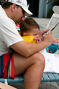 Father and son relaxing with newspaper at condo pool on Gulf of Mexico coast.  Indian Shores Tampa Bay Area Florida USA