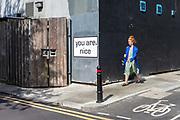 A woman walks past a humorous slogan on a street in Shoreditch, London, United Kingdom.