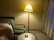 hotel room during the evening with one chair facing the window