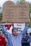 "Apr. 15, 2009 -- PHOENIX, AZ: A man holds up the Ten Commandments during the ""Tea Party"" at the Arizona State Capitol in Phoenix Wednesday. Nearly 10,000 people attended the rally, which was supposed to be in opposition to the Obama economic plan but turned into a general anti-Obama rally.  Photo by Jack Kurtz"