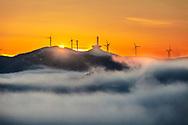 Wind generators around a memorial at sunrise