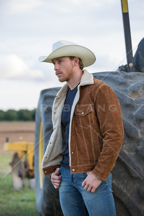 cowboy in a sheepskin coat on a ranch at sunset