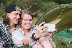 Young couple smiling and taking selfie with smart phone in front of camp tent, Bavaria, Germany