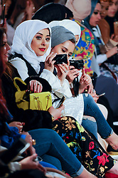 © Licensed to London News Pictures. 18/02/2017. London, UK.  Audience members watch the catwalk at the UK's first London Modest Fashion Week taking place this weekend at the Saatchi Gallery.  The two day event sees 40 brands from across the world come together to showcase their collections for Muslim and other religious women. Photo credit : Stephen Chung/LNP