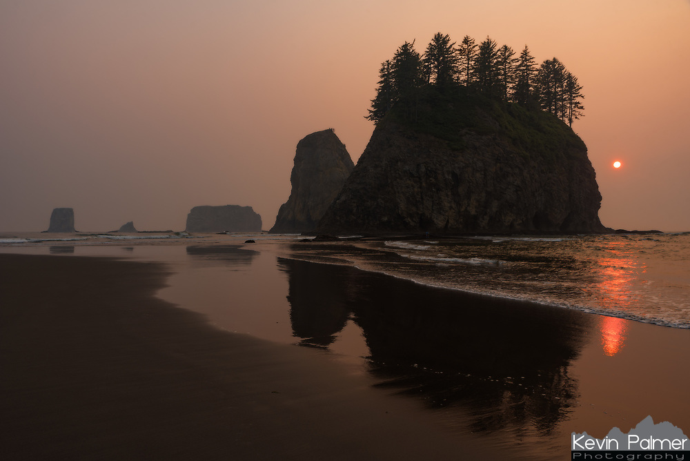 The beaches of Olympic National Park in northwest Washington are a special place. There are few stretches of coastline in the US that are this wild and undeveloped. Sea stacks dot the shoreline, some with trees growing on them. Many of the sea stacks are cut off at high tide, but can be reached at low tide. I spent the night on this beach, pitching my tent on the sand above the high-tide mark. Thick forests grow in the area, and rivers carry fallen trees out to sea. This leads to big piles of logs that have to be climbed over to reach most of the beaches. The sun didn't really set this evening. There wasn't a cloud in the sky, but the red sun disappeared early into the thick smoke. The next morning it felt like I woke up on a different beach since the marine layer came in and the fog hid all the sea stacks from view.