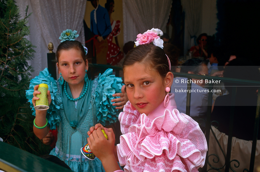 Two young flamenco-dressed sisters drink outside a caseta (marquee) during the Spring Feria in Seville. ..It is a lively event that Seville holds annually in the vast fairground area on the far bank of the Guadalquivir River. Rows of temporary marquee casetas, host families, corporations and friends into the late hours during the April Fair which begins begins two weeks after the Semana Santa, or Easter Holy Week in the Andalusian capital.