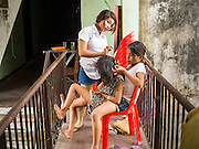 24 FEBRUARY 2015 - PHNOM PENH, CAMBODIA: Girls do each others hair on a staircase landing in the White Building. The White Building, the first modern apartment building in Phnom Penh, originally had 468 apartments, and was opened the early 1960s. The project was overseen by Vann Molyvann, the first Cambodian architect educated in France. The building was abandoned during the Khmer Rouge occupation. After the Khmer Rouge were expelled from Phnom Penh in 1979, artists and dancers moved into the White Building. Now about 2,500 people, mostly urban and working poor, live in the building. Ownership of the building is in dispute. No single entity owns the building, some units are owned by their occupants, others units are owned by companies who lease out apartments. Many of the original apartments have been subdivided since the building opened and serve as homes to two or three families. The building has not been renovated since the early 1970s and is in disrepair. Phnom Penh officials have tried to evict the tenants and demolish the building but residents refuse to move out.   PHOTO BY JACK KURTZ