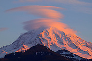 A stack of lenticular clouds seems to hover over Mt. Rainier in this winter sunset viewed near Evans Creek.