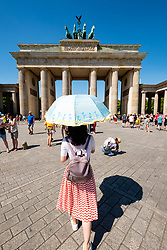 Chinese tourist with sun parasol in front of Brandenburg Gate in Berlin, Germany