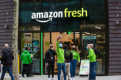 "© Licensed to London News Pictures. 16/03/2021. LONDON, UK.  Staff take a selfie outside the new 2,500 sq ft Amazon Fresh store in Wembley Park, west London on its opening day. It is the second ""just walk out"" grocery store in the UK after the opening of the Wembley branch.  As a ""contactless"" shop, it is available to anyone signed up to Amazon and with the app on their smartphone.  In-store cameras and artificial intelligence monitor customers picking up items who simply walk out and billing takes place later automatically.  Photo credit: Stephen Chung/LNP"
