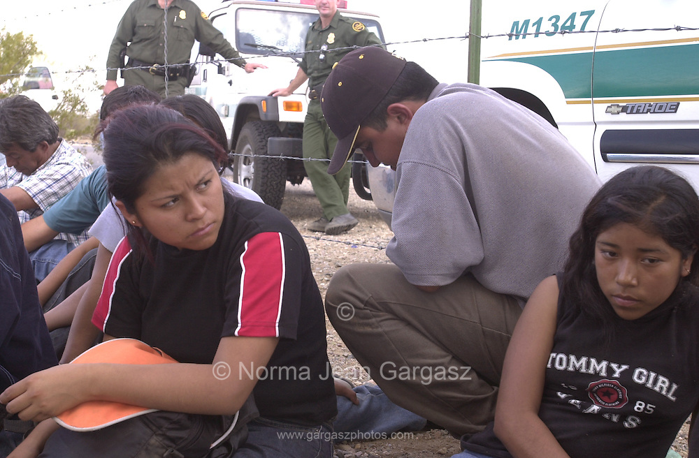 """A man, center, identified by a Border Patrol agent as """"the smuggler"""" and """"driver"""" of one of three vehicles stuffed with entrants apprehended by agents on Route 19 on the Tohono O'odham Reservation squats near a fence at the U. S. Customs office in Sells.  Four other vehicles that caravaned from an area near the San Miguel gate where they crashed the Mexico border fence managed to elude agents.  (PHOTO: NORMA JEAN GARGASZ)"""