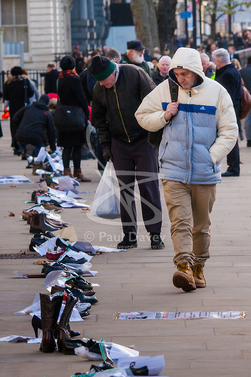 London, December 10th 2014. The shoes of hundreds of victims who died in Ireland, North and South during the Troubles are lined up opposite Downing Street as families demand that a proper investigation into over 3,600 deaths and 40,000 injuries on all sides, sets the truth free. PICTURED: A pedestrian passes the long line of shoes on Richmond Terrace.