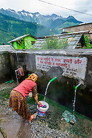 Local people get water and do dishes at a communal water tap at a hot springs, Bashisht, near Manali, Himachal Pradesh, India.