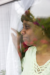 Older woman pulling back her curtain to look out the window,