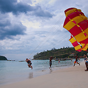 Man taking off with parachute on Karon beach, Phuket, Thailand