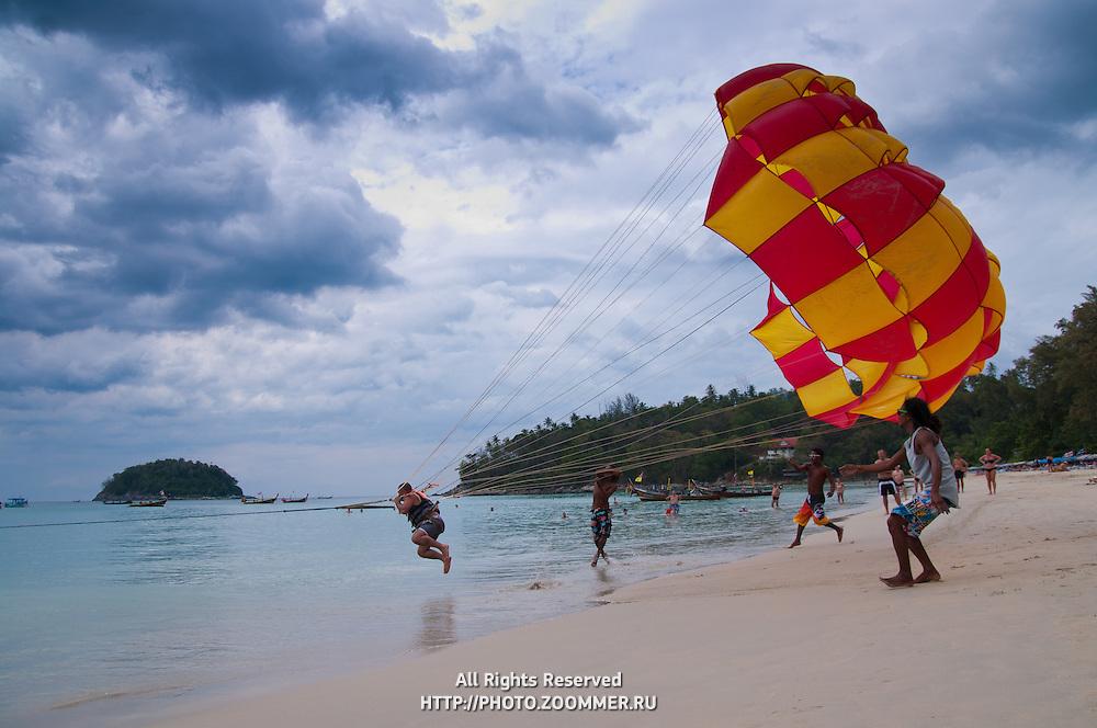 Man taking off with parachute on Karon beach, Phuket, Thailand
