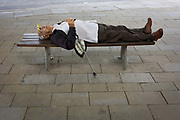 Guarding his walking stick, an elderly gentleman takes forty winks and sleeps on a city street bench in central London. With glasses in an up position on his head, the man holds his stick that keeps him stable when walking. Obviously needing a rest during a warm afternoon in the metropolis, the man takes a few moments to recoup some much-needed energy.