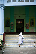 A nun walks up the steps of the cathedral, Chandannagar, India