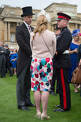 The Duke of Cambridge talks to guests during a garden party at Buckingham Palace in London.