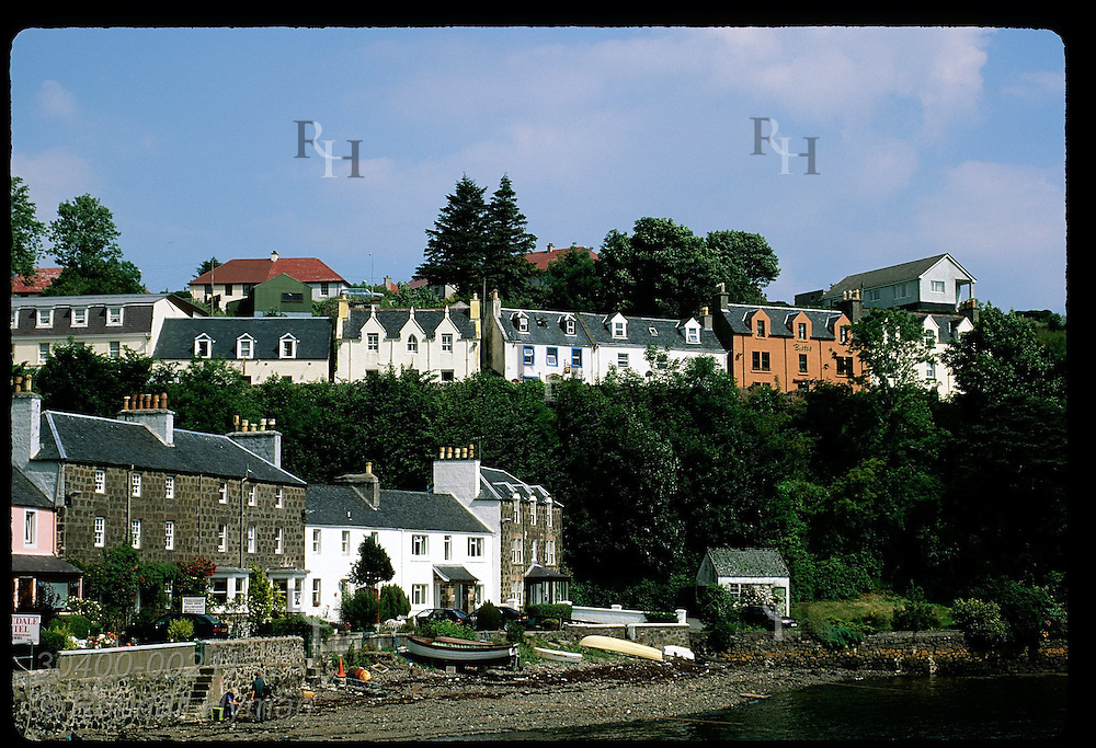 Buildings line the wharf and bluff of Portree's harbor on a sunny July morn; Isle of Skye. Scotland