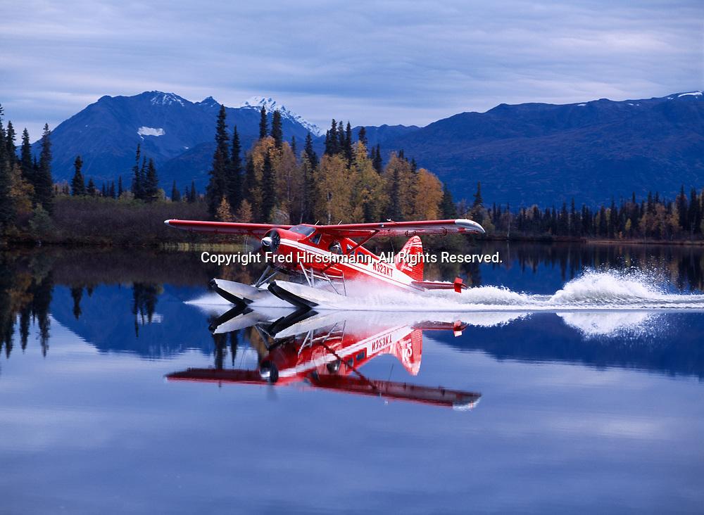K2 Aviation's de Havilland Beaver landing on glassy water of Finger Lake by Winterlake Lodge, Alaska.