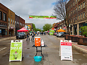 23 MAY 2020 - AMES, IOWA: Signs and a hand washing station welcome shoppers to the Farmers' Market in downtown Ames. The Ames Main Street Farmers' Market reopened Saturday after nearly a month of only online sales because of Iowa's bans on large gatherings caused by the COVID-19 pandemic. Only about 15 venders set up stalls Saturday and attendance was significantly lower than normal. All of the venders wore face masks and many, but not all, of the shoppers wore face masks. Farmers' markets are popular community gatherings in Iowa, but they've been on hiatus since the Coronavirus (SARS-CoV-2) pandemic. At this time, Iowa farmers' markets are not allowed to have entertainment or sell non-food or non-agricultural goods.          PHOTO BY JACK KURTZ