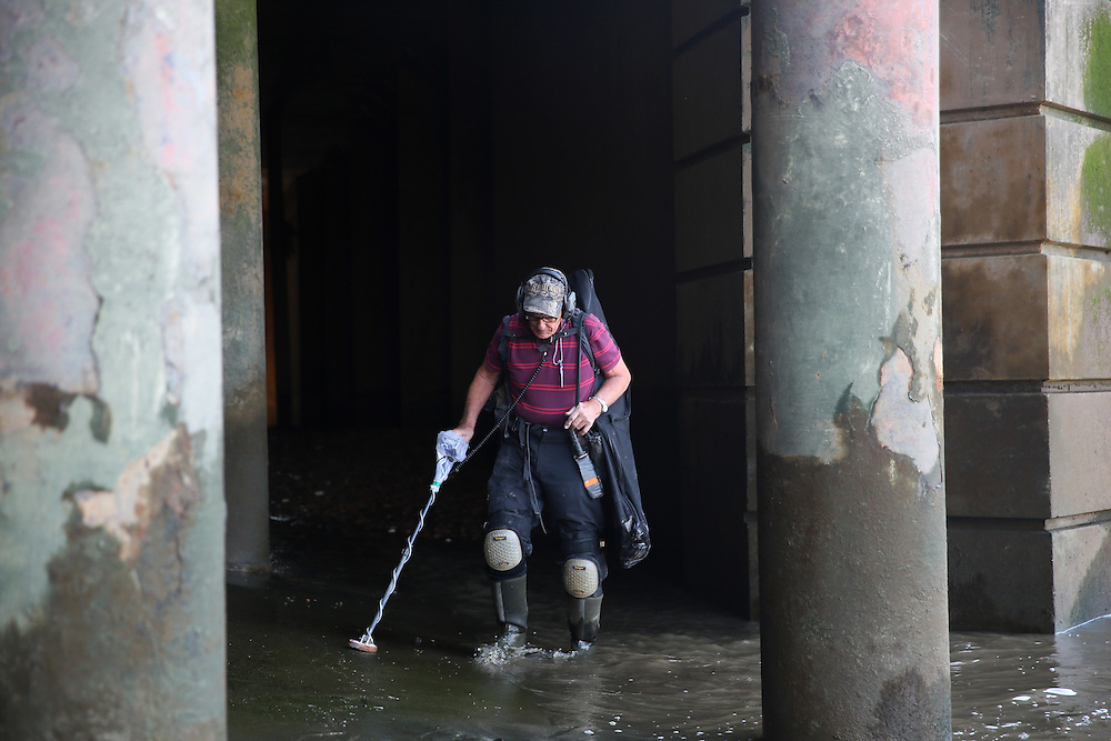"""Mudlarker Malcolm """"Mack"""" Macduff uses a metal detector as he looks for items on the banks of the River Thames in London, Britain May 24, 2016. When the river Thames is at low tide, mudlarkers scour the shore for historical artefacts and remains from there City of London's ancient past. Finds can date back to Roman times to when the city was found up until more recent times. Anyone can walk along the river and look for finds, but the uses of metal detectors and digging is restricted. Mudlarkers need to be licences by the Port of London Authority. All find should be register with the Museum of London. REUTERS/Neil Hall"""