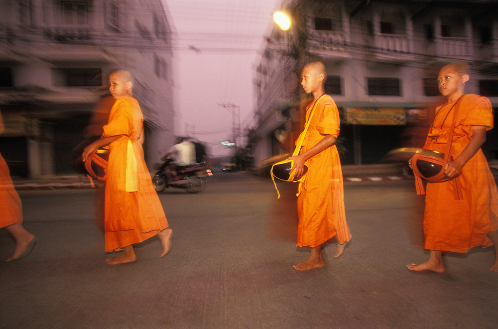 Novice monks walk the streets with their food bowls early in the morning, Mae Hong Son, Thailand. People will stop them on the way to put food into their bowls as an offering.