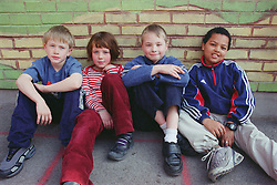 Multiracial group of children sitting together in school playground; leaning against brick wall,