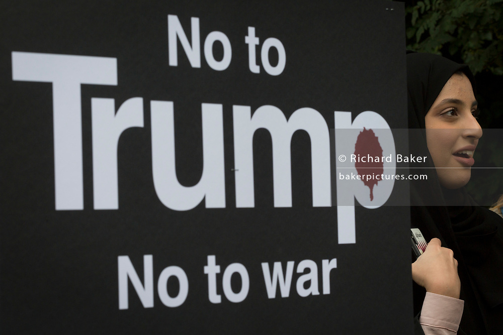 A Muslim protestor outside a temporary perimeter fence encircling Winfield House, the official residence of the US Ambassador during the visit to the UK of US President, Donald Trump, on 12th July 2018, in Regent's Park, London, England.