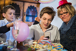 Teenager with grandmother using smartphone at party