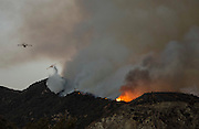 SuperScoopers firefighting planes drop water during a brushfire in San Gabriel Canyon above Azusa, California, Monday, September 23, 2013.  A fire that began above Azusa burned north into the Angeles National Forest and was growing. The fire started at 5:56 p.m. and county firefighters fought the blaze with SuperScoopers, helicopters and ground forces. (Photo by Ringo Chiu/PHOTOFORMULA.com)