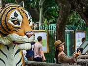 17 AUGUST 2018 - BANGKOK, THAILAND:   A woman takes a selfie with her smart phone in front of a cement statue of a tiger in the predator display at Dusit Zoo in Bangkok. The zoo opened in 1938. The zoo grounds were originally the Dusit Royal Garden. The zoo is scheduled to close by the end of August 2018 because it is being relocated to Nakhon Pathom province, south of Bangkok.     PHOTO BY JACK KURTZ