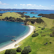 An aerial view of a secluded beach in the Bay of Islands, North Island, New Zealand. .The Bay of Islands boasts a unique coastline sheltering over 150 small islands in its arms. Once a seafaring and whaling region the Bay of Islands is today a popular tourist destination recognised for it's cultural heritage as well as it's amazing scenery and wildlife. Small towns are scattered along the coastline. There are a lot of water-based activities, including kayaking, swimming with dolphins, game fishing and boating and whales and dolphins can often be seen in the bay. Bay of Islands, New Zealand, 16th November 2010. Photo Tim Clayton.