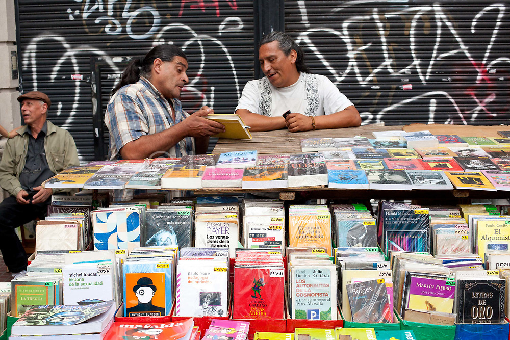 Two Argentinian men talking at a book stall in San Telmo market, Buenos Aires, Argentina. .