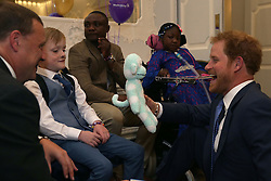 Prince Harry (right) reacts as he greets Inspirational Child Award Winner Samuel Merrick (second left), and his father Paul (left), as he attends the WellChild Awards in London. The awards recognise the courage of seriously ill children, their families and carers.