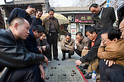 People gather to play Xiangqi, Chinese chess, on pavement by the City Wall, Xian, China